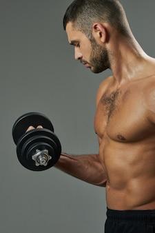 Очаровательны спортсмен человек, тонизирующий мышцы в комнате в помещении