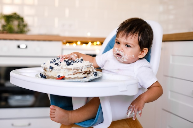 첫 번째 생일을 축하하고 첫 번째 케이크를 먹는 사랑스러운 아기. 풍선으로 장식 된 아이 생일 파티. 케이크를 먹는 아이.