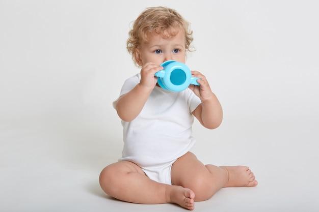 Очаровательный мальчик пьет воду из бутылочки для кормления, смотрит в сторону, в боди, сидит на полу босиком, держит бутылку обеими руками, позирует у светлой стены.