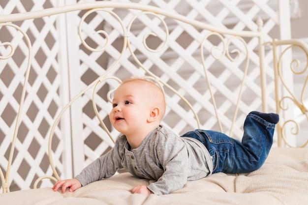 白い日当たりの良い寝室で愛らしい男の子。ベッドでリラックスした新生児。幼児のための保育園。子供のためのテキスタイルと寝具。家で家族の朝。おもちゃのクマとおなかの時間の間に生まれたばかりの子供。