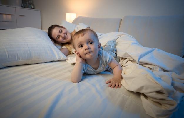 眠ろうとしている母親の隣のベッドに横たわっている愛らしい男の子