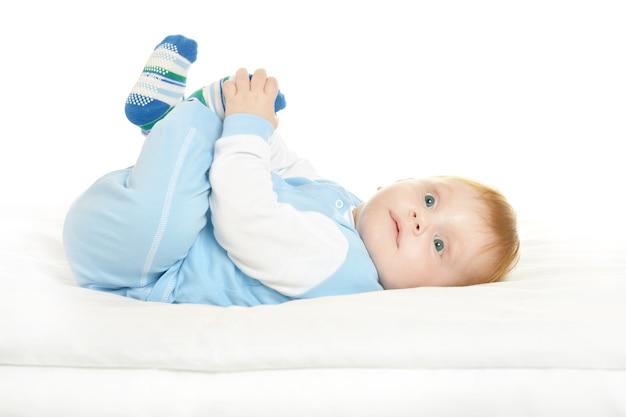 白い背景の上の毛布の上の愛らしい男の子