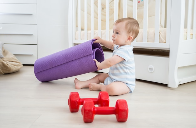 Adorable baby boy playing with dumbbells and fitness mat at living room