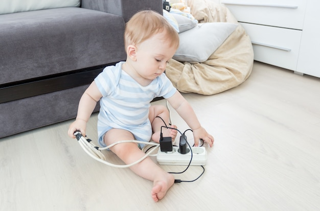 Adorable baby boy playing with electrical extension and wires on floor