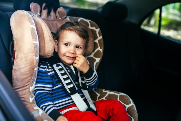 Adorable baby boy in a safety car seat.