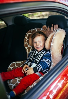 Adorable baby boy in a safety car seat