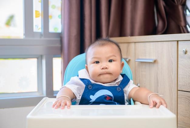 高い椅子に座って、お気に入りの離乳食を待っている愛らしい男の子