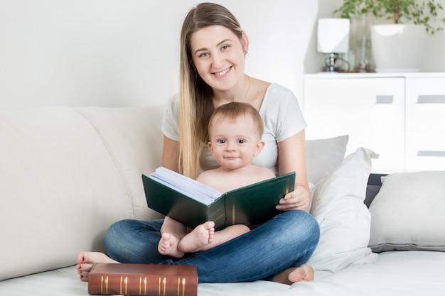 母親の膝の上に座って大きな本を見ている愛らしい男の子