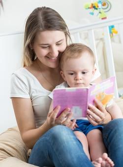 Очаровательный мальчик сидит на коленях матери и читает книгу