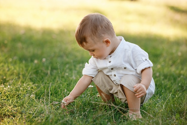 公園の芝生の上に座っているかわいい男の子