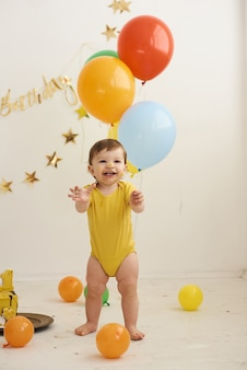 Adorable baby boy wearing yellow body and eating a small birthday cake.