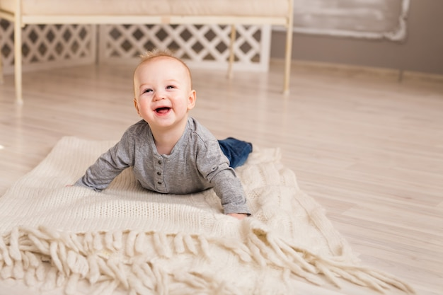 Adorable baby boy in white sunny bedroom. newborn child. nursery for young children. family morning at home.