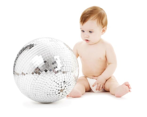 Очаровательный мальчик с большим диско-шаром над белой