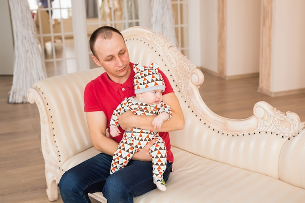 Adorable baby boy with blue eyes. newborn child and father.