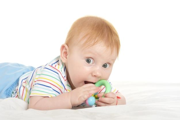 白い背景の上の毛布におもちゃで愛らしい男の子