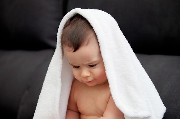 사랑스러운 아기는 수건으로 덮여