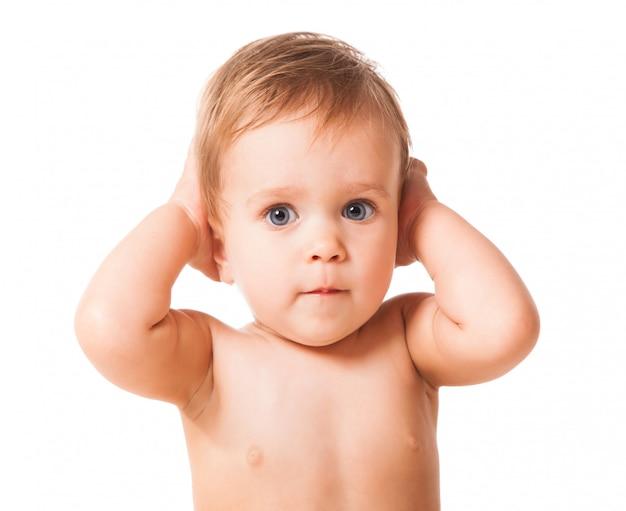 Очаровательный малыш закрывает уши руками