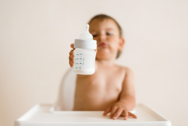 Прелестный ребенок пить молоко из бутылки из бутылки.