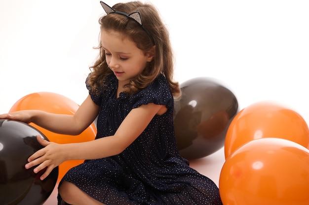Очаровательная девочка, 4-летний ребенок в вечернем платье и обруч с кошачьими ушами, весело играя с ярко-оранжевыми и черными воздушными шарами на белом фоне с копией пространства. концепция хэллоуина