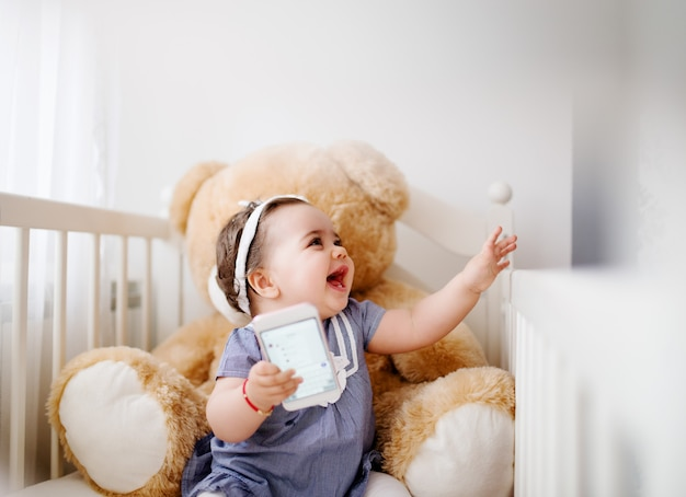 Adorable baby girl in a crib. laughing and playing with smart phone.