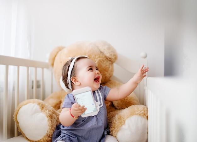 침대에서 사랑스러운 아기 소녀입니다. 웃으면 서 스마트 폰으로 놀기.