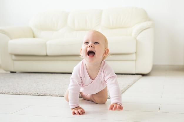 사랑스러운 아기 소녀 흰색 맑은 방에서 크롤링 학습.