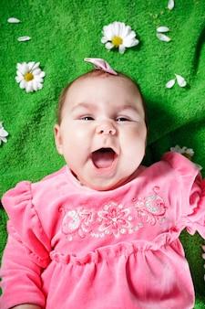 牧草地と笑顔に横たわっている愛らしい女の赤ちゃん