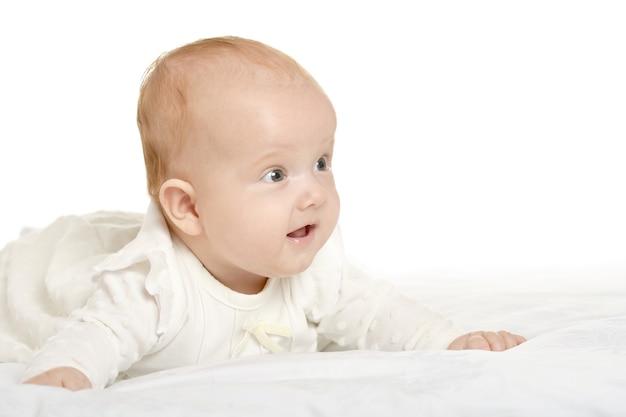 白い背景の上の毛布の上の愛らしい女の赤ちゃん