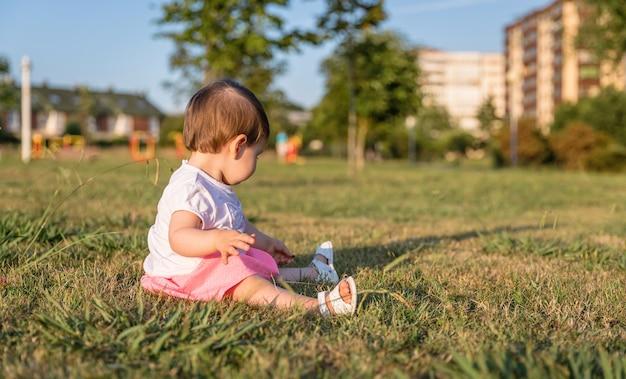 화창한 여름날 잔디 공원에 앉아 노는 사랑스러운 아기 소녀