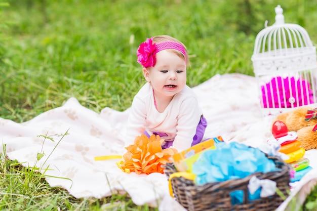 愛らしい赤ちゃん女の子笑顔ピクニック遊び心のある週末の自然