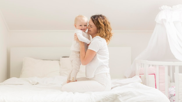 Adorable baby girl together with mother at home