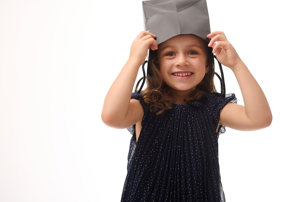 Adorable baby girl, winsome child puts a shopping black packet on head, smiles toothy smile, rejoices, has fun looks at camera, posing against white background with copy space. black friday concept