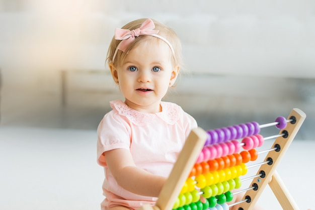Adorable baby girl with educational toy scores in home or kindergarten