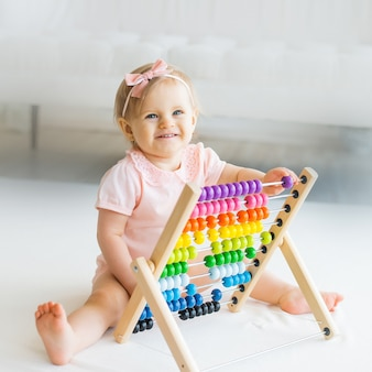 Adorable baby girl with educational toy scores in home