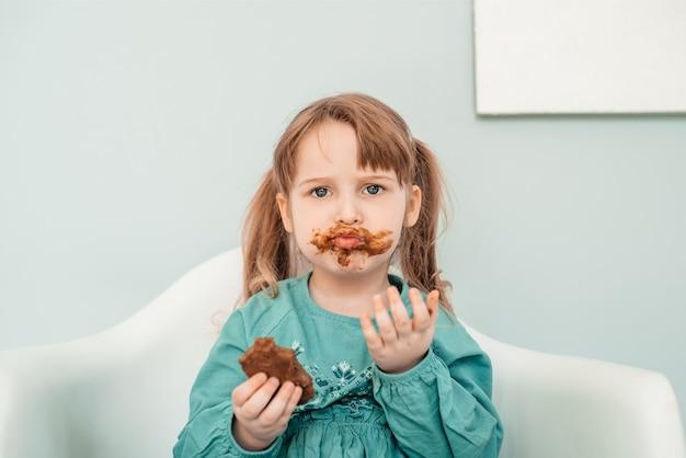 얼굴을 가진 사랑스러운 아기 소녀 초콜릿으로 덮여 있습니다. 프리미엄 사진