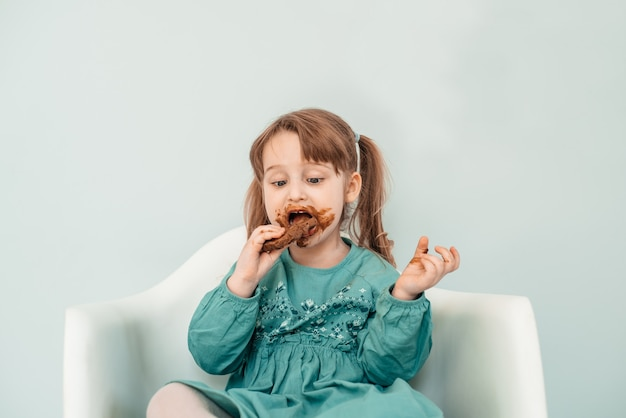 얼굴을 가진 사랑스러운 아기 소녀 초콜릿으로 덮여 있습니다.