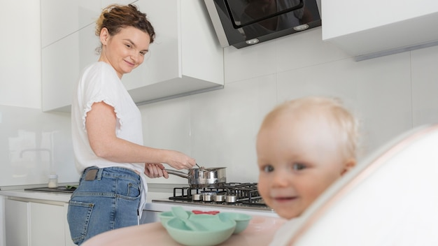 Adorable baby girl with mother in the kitchen