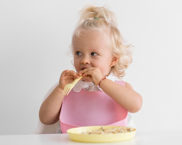 Adorable baby playing with food