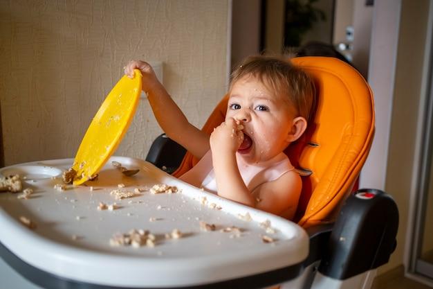 Очаровательный ребенок играет с пластиковой тарелкой за столом маленький ребенок балуется детским стульчиком после еды