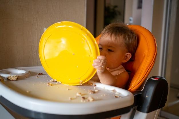 Очаровательный ребенок играет с пластиковой тарелкой за столом. маленький ребенок балуется детским стульчиком после еды