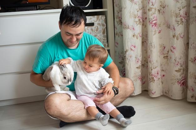 사랑스러운 아기는 아빠의 팔에 앉아 장식용 토끼 가축을 가족과 함께 쓰다듬습니다