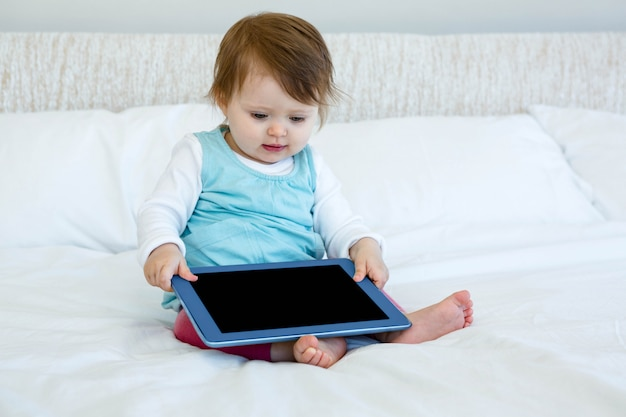Adorable baby sitting on a bed holding a computer tablet