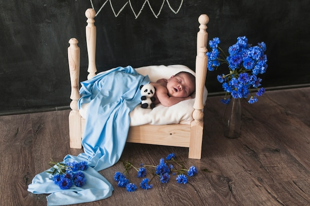 Adorable baby in small bed