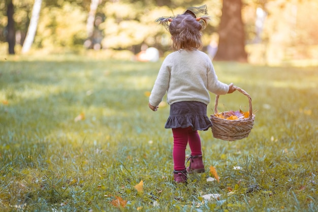 Adorable baby walks out in the park with a basket of yellow autumn leaves toddler in a witch costume