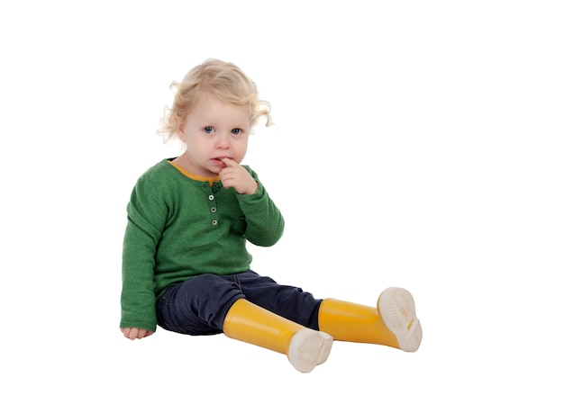 Adorable baby with yellow gumboots