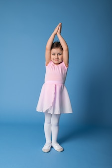 ピンクのドレスを着た愛らしいバレリーナが立って腕を上げ、体を伸ばします。