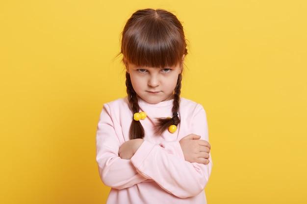 Очаровательная красивая маленькая обиженная девочка над желтым