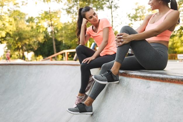 운동복에 사랑스러운 아름다운 여성이 앉아서 콘크리트 운동장에 물병으로 이야기