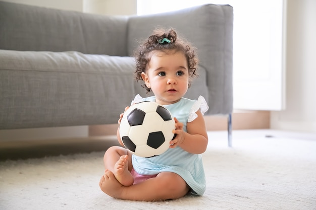 Adorable black haired baby girl in pale blue clothes sitting on floor at home, looking away, playing soccer ball. kid at home and childhood concept