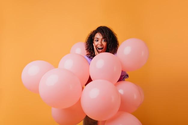Adorabile donna di colore che gode della festa con il sorriso. incantevole modello femminile con palloncini di elio rosa in piedi sull'arancio.